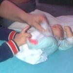 Met grote broer babyverzorging oefenen op een babypop, jaja